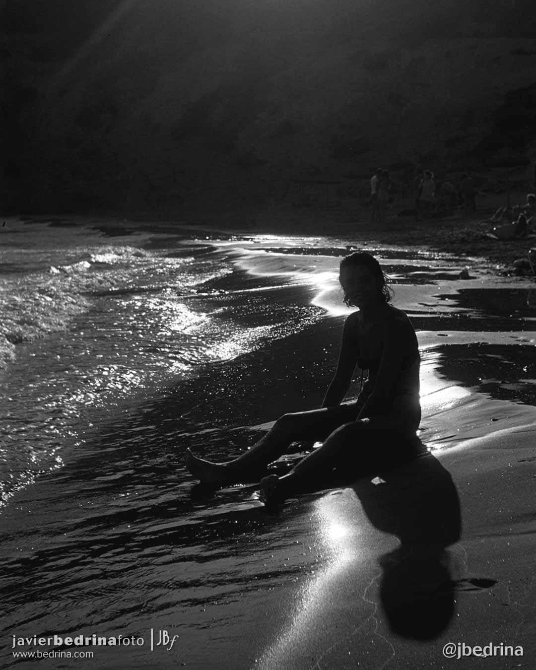 Contraluz en la playa. Sentada en la orilla.